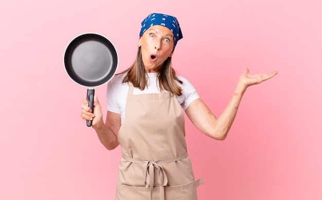 Mooie vrouw van middelbare leeftijd die verrast en geschokt kijkt, met open mond terwijl ze een voorwerp vasthoudt en een pan vasthoudt. chef-kok concept
