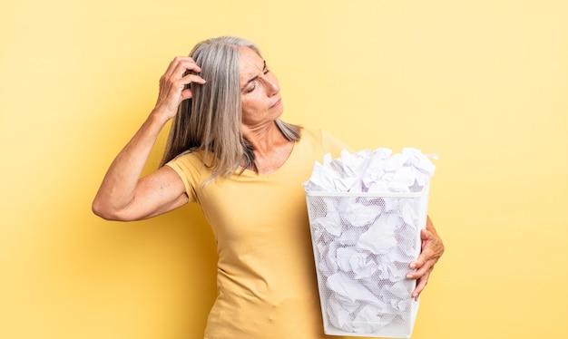 Mooie vrouw van middelbare leeftijd die vrolijk lacht en dagdroomt of twijfelt. papieren ballen mislukking concept