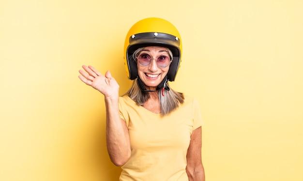 Mooie vrouw van middelbare leeftijd die vrolijk lacht, met de hand zwaait, je verwelkomt en begroet. motorhelm concept