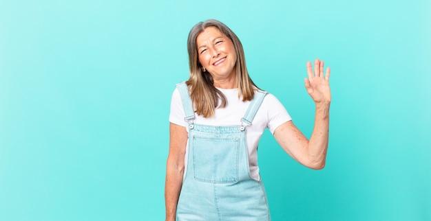 Mooie vrouw van middelbare leeftijd die vrolijk lacht, met de hand zwaait, je verwelkomt en begroet