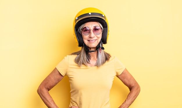 Mooie vrouw van middelbare leeftijd die vrolijk lacht met een hand op de heup en zelfverzekerd. motorhelm concept