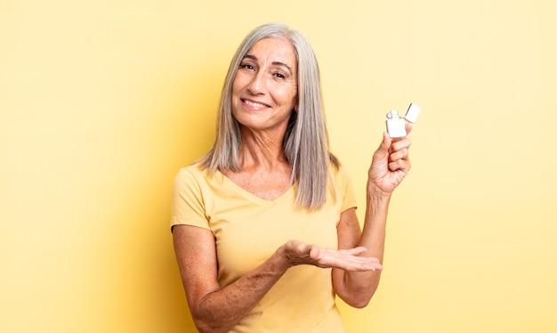Mooie vrouw van middelbare leeftijd die vrolijk lacht, zich gelukkig voelt en een concept toont. lichter concept