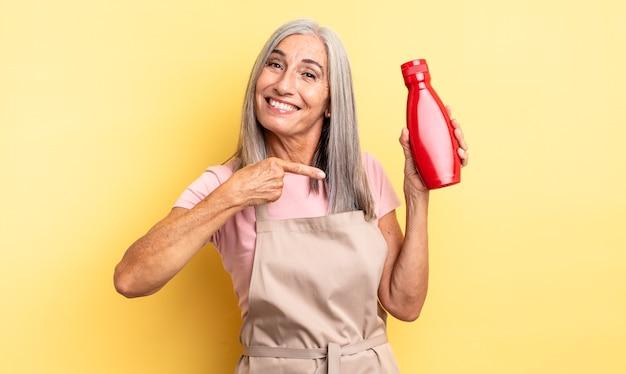 Mooie vrouw van middelbare leeftijd die vrolijk lacht, zich gelukkig voelt en naar de zijkant wijst. ketchup-concept