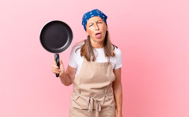 Mooie vrouw van middelbare leeftijd die walgt en geïrriteerd voelt en een tong uitsteekt en een pan vasthoudt. chef-kok concept