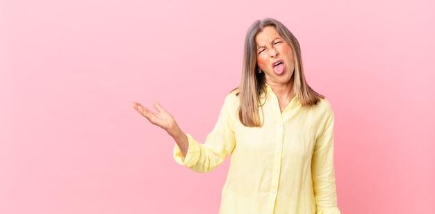 Mooie vrouw van middelbare leeftijd die walgt en geïrriteerd voelt en tong uitsteekt