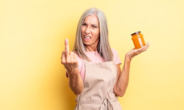 Mooie vrouw van middelbare leeftijd die zich boos, geïrriteerd, opstandig en agressief voelt. perzik jam