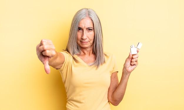 Mooie vrouw van middelbare leeftijd die zich boos voelt en duimen naar beneden laat zien. lichter concept