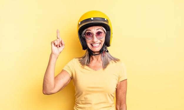 Mooie vrouw van middelbare leeftijd die zich een gelukkig en opgewonden genie voelt na het realiseren van een idee. motorhelm concept