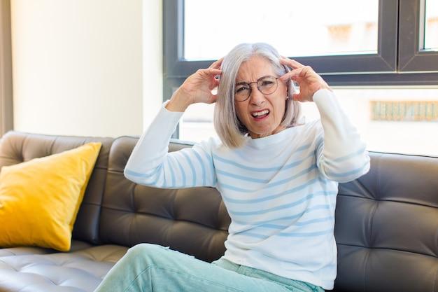 Mooie vrouw van middelbare leeftijd die zich gefrustreerd en geïrriteerd voelt, ziek en moe van mislukking, beu met saaie, saaie taken