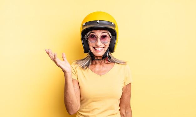 Mooie vrouw van middelbare leeftijd die zich gelukkig, verrast voelt en een oplossing of idee realiseert. motorhelm concept