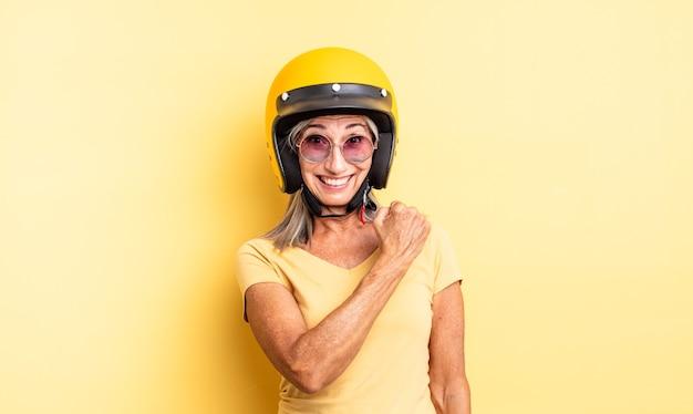 Mooie vrouw van middelbare leeftijd die zich gelukkig voelt en een uitdaging aangaat of viert. motorhelm concept