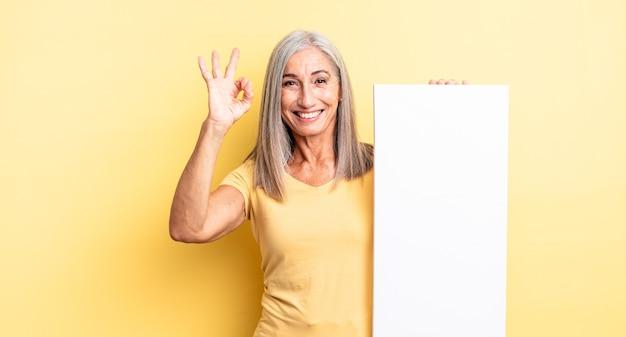 Mooie vrouw van middelbare leeftijd die zich gelukkig voelt, goedkeuring toont met een goed gebaar. leeg canvasconcept