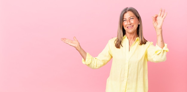 Mooie vrouw van middelbare leeftijd die zich gelukkig voelt, goedkeuring toont met een goed gebaar