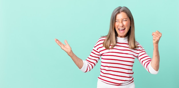 Mooie vrouw van middelbare leeftijd die zich geschokt voelt, lacht en succes viert