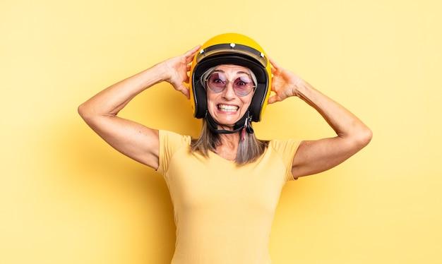 Mooie vrouw van middelbare leeftijd die zich gestrest, angstig of bang voelt, met de handen op het hoofd. motorhelm concept