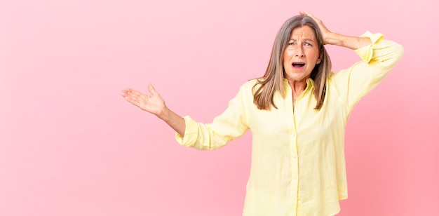 Mooie vrouw van middelbare leeftijd die zich gestrest, angstig of bang voelt, met de handen op het hoofd
