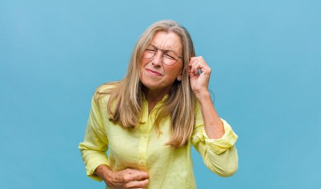 Mooie vrouw van middelbare leeftijd die zich gestrest en gefrustreerd voelt, de handen naar het hoofd steekt, zich moe, ongelukkig en met migraine voelt