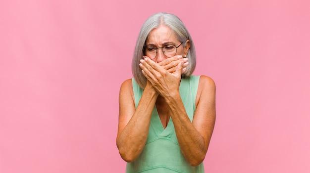 Mooie vrouw van middelbare leeftijd die zich gestrest, gefrustreerd en moe voelt, pijnlijke nek wrijft, met een bezorgde, onrustige blik