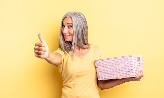 Mooie vrouw van middelbare leeftijd die zich trots voelt, positief glimlacht met duimen omhoog. leeg mandconcept