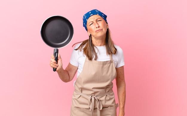 Mooie vrouw van middelbare leeftijd die zich verdrietig en zeurt met een ongelukkige blik en huilt en een pan vasthoudt. chef-kok concept