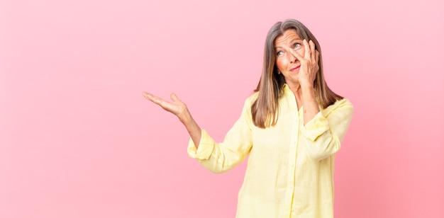 Mooie vrouw van middelbare leeftijd die zich verveeld, gefrustreerd en slaperig voelt na een vermoeiende