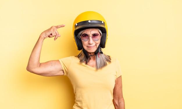 Mooie vrouw van middelbare leeftijd die zich verward en verbaasd voelt en laat zien dat je gek bent. motorhelm concept