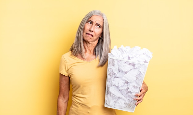 Mooie vrouw van middelbare leeftijd die zich verward en verward voelt. papieren ballen mislukking concept