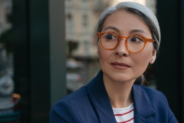 Mooie vrouw van middelbare leeftijd dragen stijlvolle bril permanent buitenshuis
