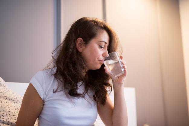 Mooie vrouw van middelbare leeftijd drinkwater zittend op het bed in pyjama.