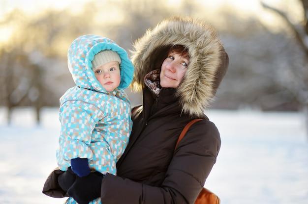 Mooie vrouw van middelbare leeftijd en haar schattige kleine kleinzoon in de winter park