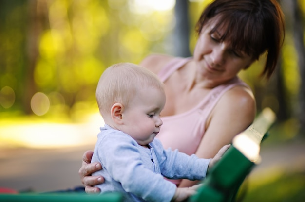 Mooie vrouw van middelbare leeftijd en haar schattige kleine kleinzoon in het zomer park