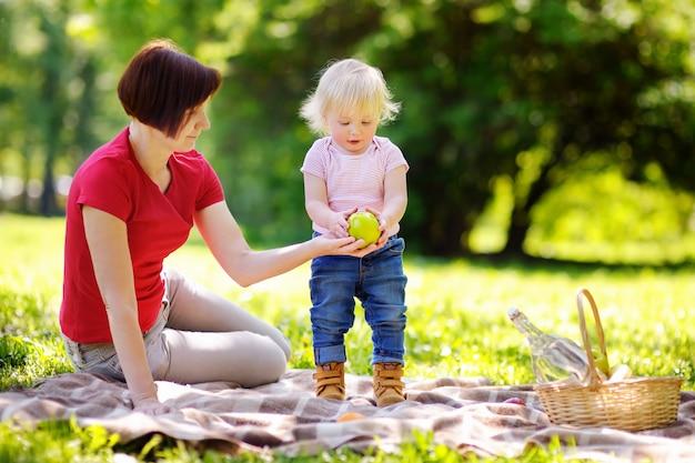 Mooie vrouw van middelbare leeftijd en haar schattige kleine kleinzoon met een picknick in het zonnige park