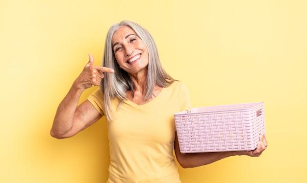 Mooie vrouw van middelbare leeftijd glimlachend vol vertrouwen wijzend naar eigen brede glimlach. leeg mandconcept