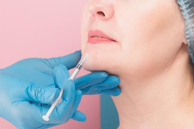 Mooie vrouw van middelbare leeftijd krijgt cosmetische injectie op de lippen, close-up.