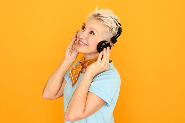 Mooie vrouw van middelbare leeftijd met blauwe ogen en kort haar poseren tegen gele achtergrond opzoeken met vrolijke blije glimlach, luisteren naar muziek met behulp van draadloze hoofdtelefoons.