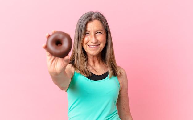 Mooie vrouw van middelbare leeftijd met een donut