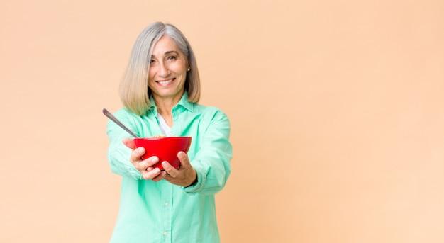 Mooie vrouw van middelbare leeftijd met een ontbijtkom