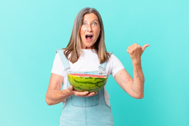 Mooie vrouw van middelbare leeftijd met een schijfje watermeloen