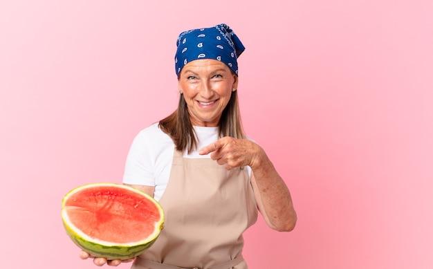 Mooie vrouw van middelbare leeftijd met een schort en een watermeloen vast