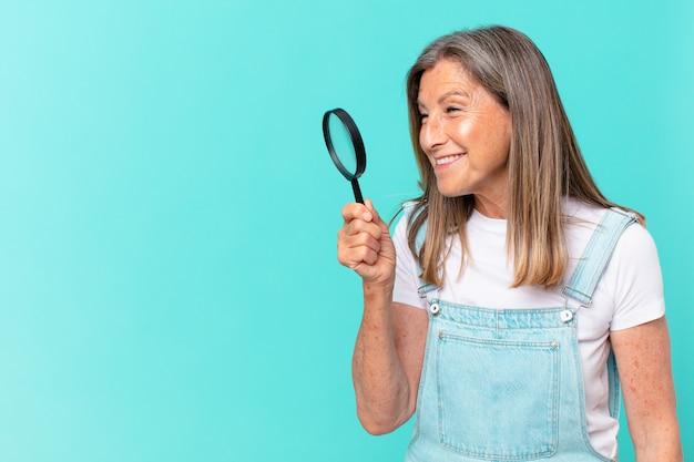 Mooie vrouw van middelbare leeftijd met een vergrootglas. zoekconcept