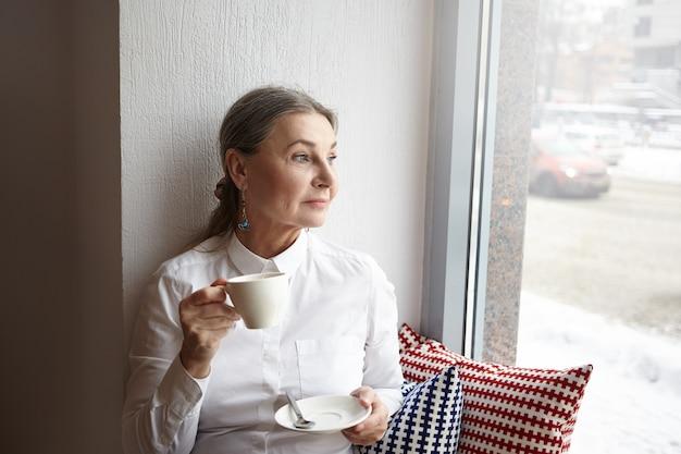 Mooie vrouw van middelbare leeftijd met grijs haar en blauwe ogen, zittend in de cafetaria op de vensterbank, genietend van koffie in de ochtend, kopje vast te houden en door raam te kijken, met doordachte gezichtsuitdrukking