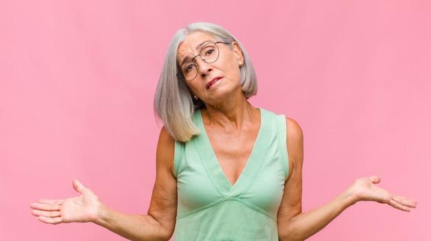 Mooie vrouw van middelbare leeftijd met handpalm tegen voorhoofd denkend oeps, na het maken van een domme fout of het herinneren, zich dom voelen