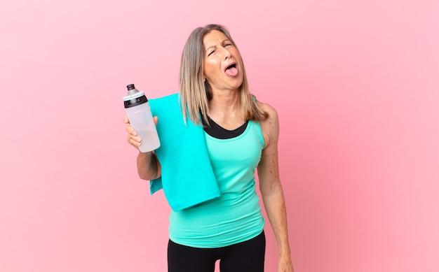 Mooie vrouw van middelbare leeftijd met vrolijke en rebelse houding, grappen maken en tong uitsteken. fitnessconcept