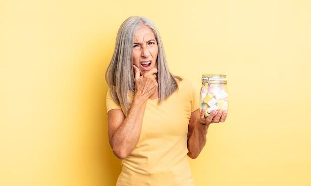 Mooie vrouw van middelbare leeftijd met wijd open mond en ogen en hand op kin. snoep fles concept