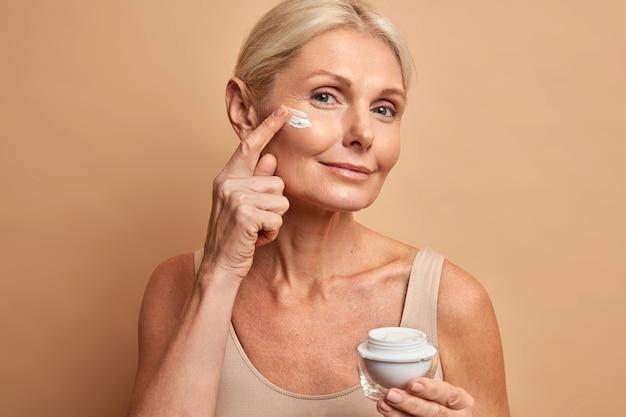 Mooie vrouw van middelbare leeftijd past anti-verouderingscrème toe op het gezicht ondergaat schoonheidsbehandelingen geeft om de huid