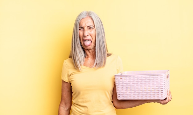 Mooie vrouw van middelbare leeftijd voelt zich walgelijk en geïrriteerd en tong uit. leeg mandconcept
