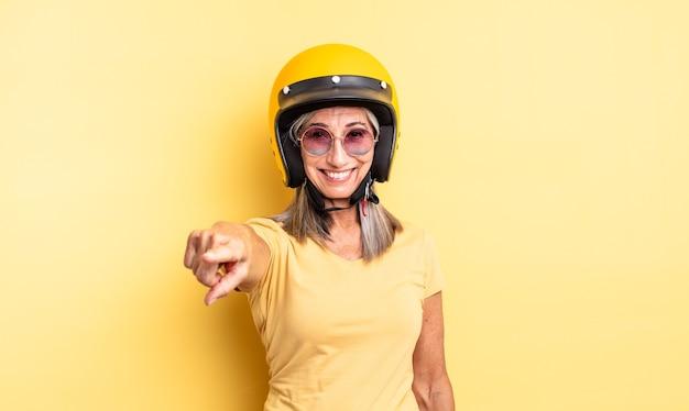 Mooie vrouw van middelbare leeftijd wijzend op de camera die jou kiest. motorhelm concept