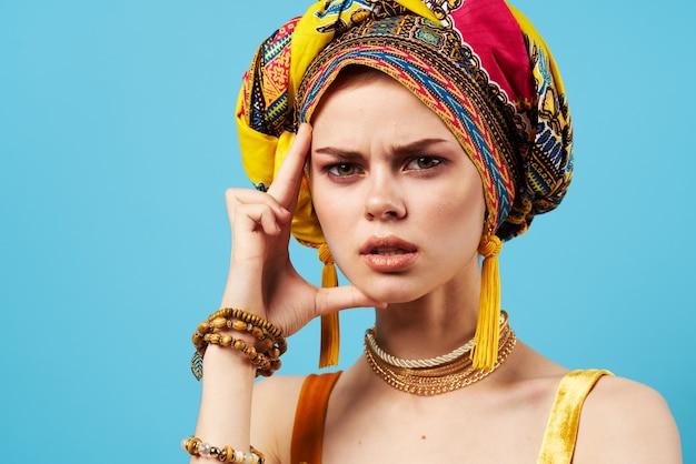 Mooie vrouw veelkleurige tulband decoratie mode close-up blauw.