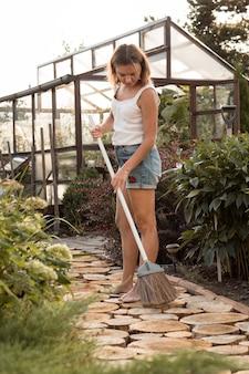 Mooie vrouw vegen pad in tuin verticale shot