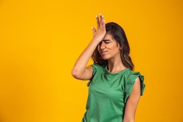 Mooie vrouw vergeten en verward op gele achtergrond